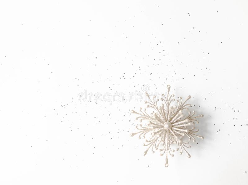 Flat lay white New year or Christmas composition - silver snowflake and confetti on a white background. Top view. Copy space. Flat lay white New year or royalty free stock photography