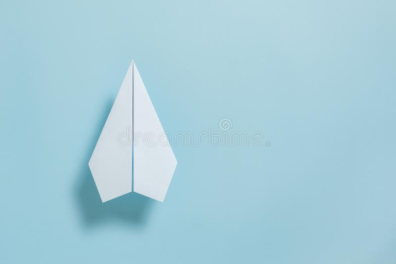Flat lay of white paper plane on pastel blue color background royalty free stock images