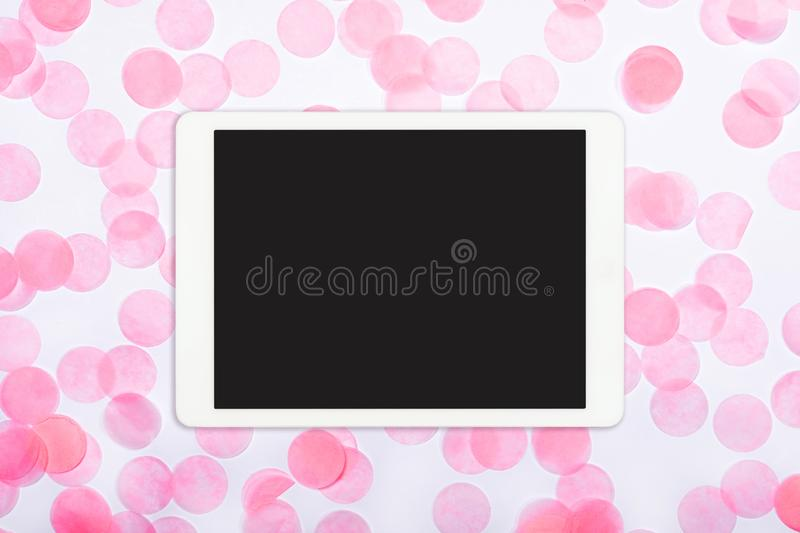 Flat lay of white touchpad with blank screen on pink confetti background stock images
