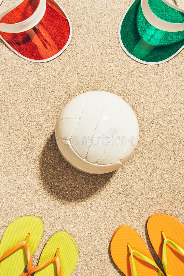 Flat lay with white volleyball ball, colorful caps and flip flops arranged. On sand stock photo