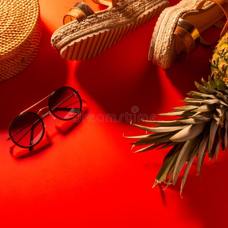 Flat lay, Wicker fashion bag, sunglasses, tropical pineapple and women`s shoes. Summer fashion, holiday concept. On a bright red royalty free stock photos