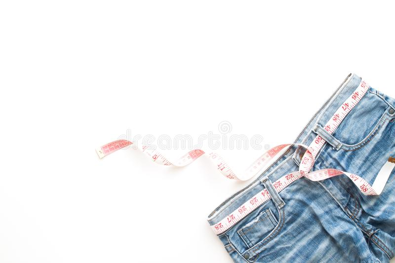 Flat lay of woman blue jeans with measuring-tape on white background, Diet and healthy lifestyle concept stock image