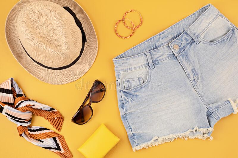 Flat lay with woman fashion accessories, jeans shorts, hat, sunglasses over yellow background. Fashion, online beauty blog, summer. Style, shopping and trends stock image