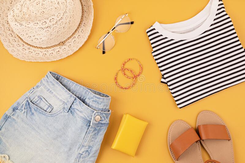 Flat lay with woman fashion accessories, jeans shorts, hat, sunglasses over yellow background. Fashion, online beauty blog, summer. Style, shopping and trends royalty free stock photos