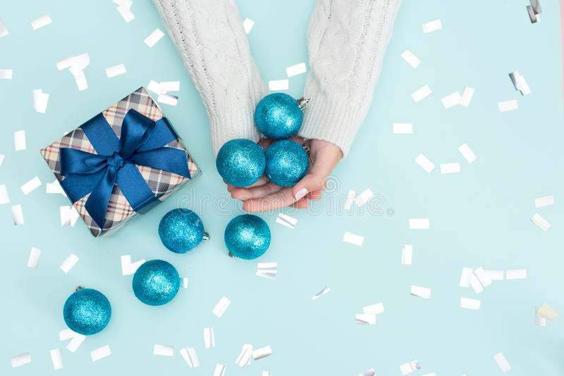 Flat lay of woman hands holding gift wrapped and decorated with bow on blue background with copy space royalty free stock photo