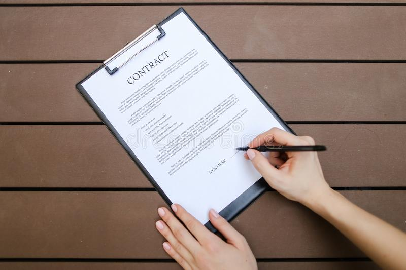 Flat lay of woman hands sign contract, wooden backgroung. Front. Beautiful flat lay of young woman hands with pen sign contract, wooden backgroung. concept of royalty free stock photos