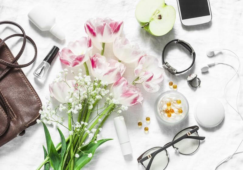 Flat lay women`s accessories set-leather bag, tulips bouquet, cosmetics, glasses, phone, apple, headphones on light background royalty free stock photo