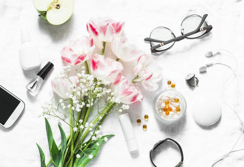 Flat lay women`s accessories set - tulips bouquet, cosmetics, glasses, phone, apple, headphones on light background top view. Bea royalty free stock photography