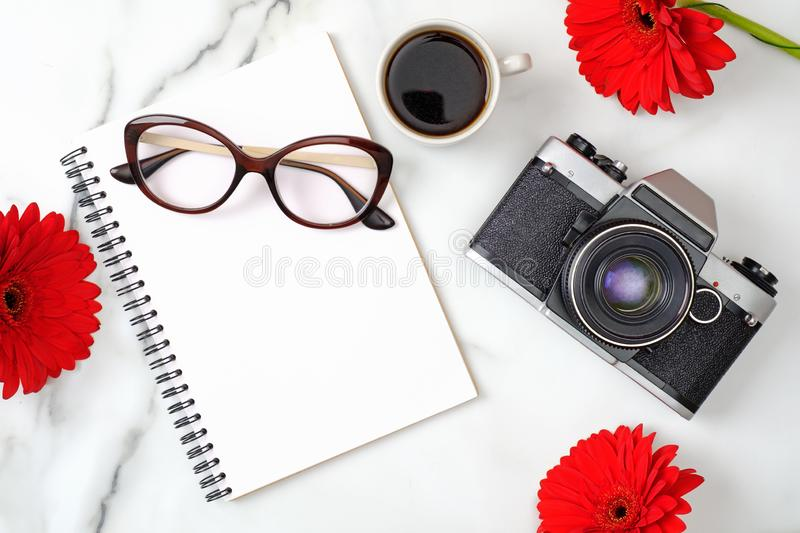 Flat lay women`s home office desk. Workspace with paper notepad, retro photo camera, coffee cup, feminine glasses and daisy stock photo