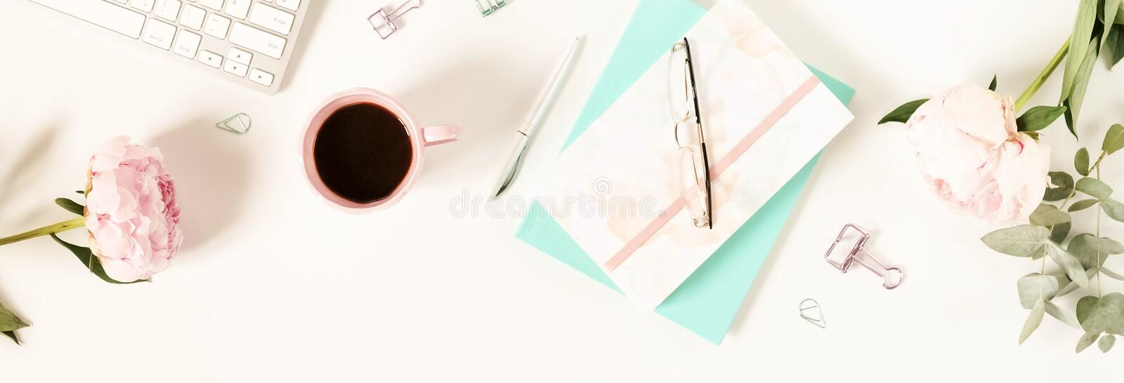 Flat lay women`s office desk. Female workspace. With laptop, flowers peonies, accessories, notebook, glasses, cup of coffee on white background. Top view stock photo