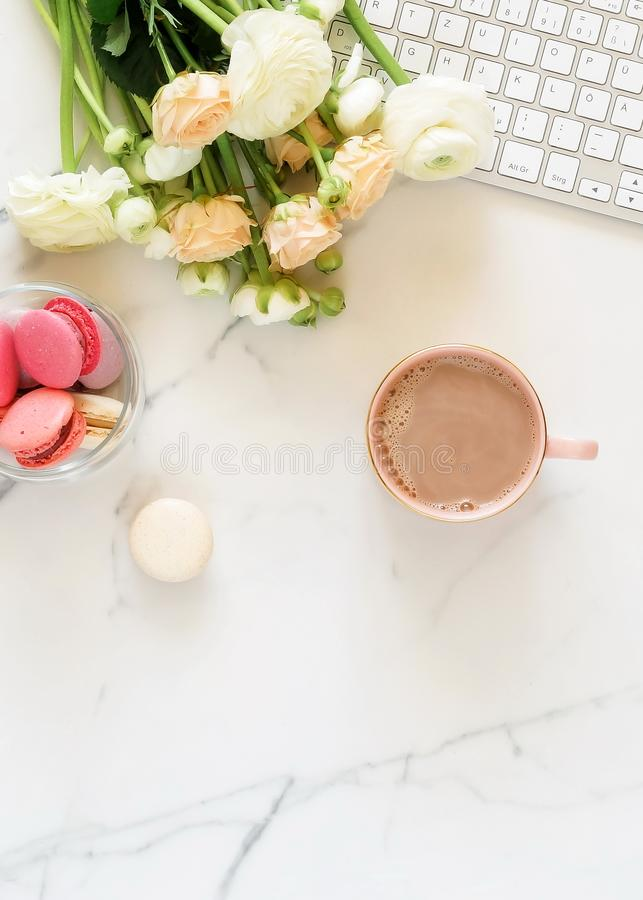 Flat lay women`s office desk. Female workspace with laptop,  flowers pink ranunkulus royalty free stock photos