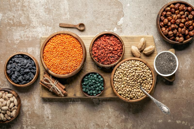 Flat lay of wooden board with legumes, goji berries and healthy ingredients. With rustic background royalty free stock photos