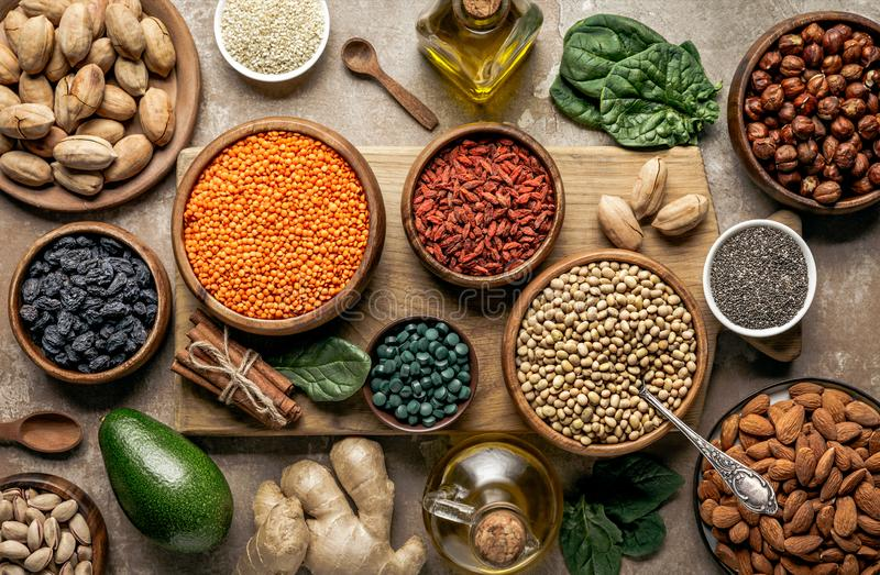 Flat lay of wooden board with legumes, goji berries and healthy ingredients. On table stock photography