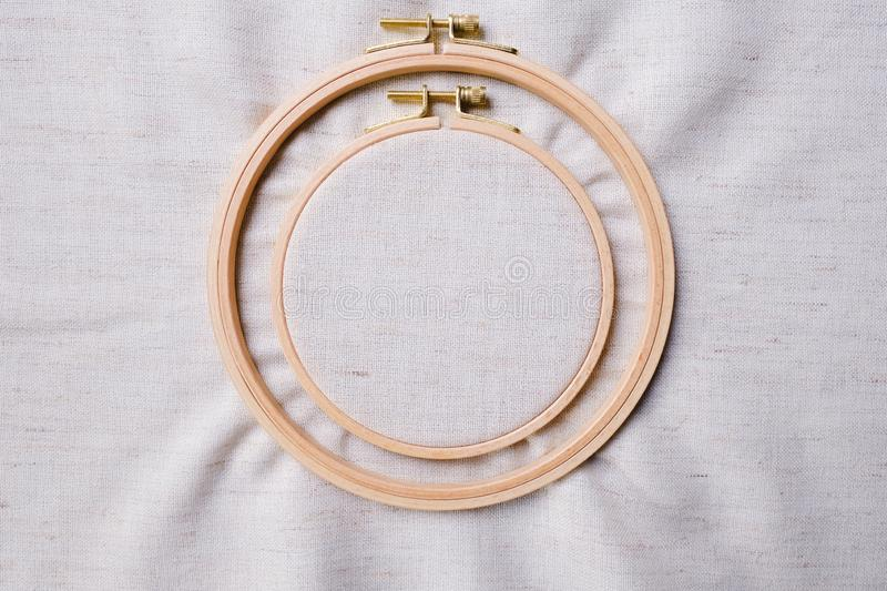 Flat lay with wooden embroidery hoops on a canvas background. Top view. Of a mockup royalty free stock photo