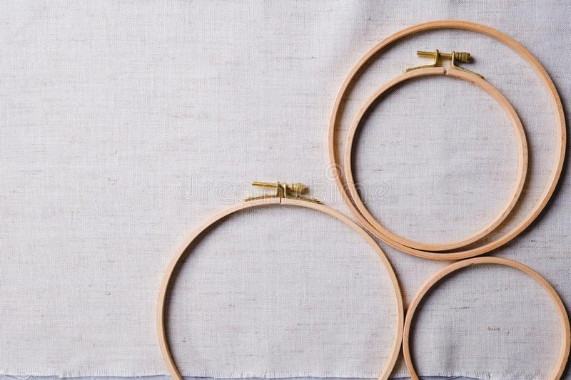 Flat lay with wooden embroidery hoops on a canvas background. Top view stock images
