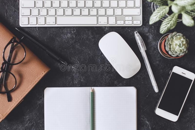 Flat lay. Office dark table with computer notepad, mouse, pen, p. Flat lay. Working place on dark table with copy space. Table with keyboard, computer, notepad royalty free stock images