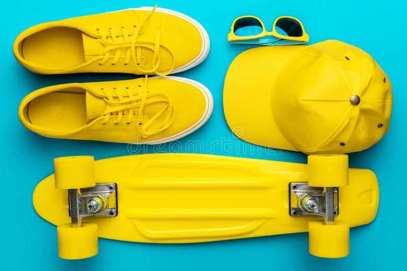 Flat lay of yellow baseball cap, sunglasses, sneakers, mini cruiser skateboard. Top view of yellow modern teenage accessories in oder. Flat lay image of yellow royalty free stock photos
