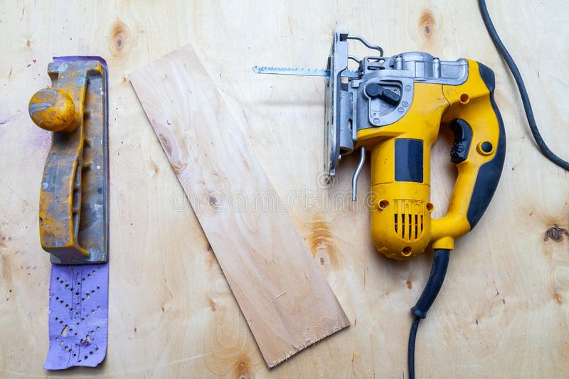 Flat lay of a yellow electric jigsaw and hand plane ready for work use on the workbench with sawn plywood in a workshop for royalty free stock images