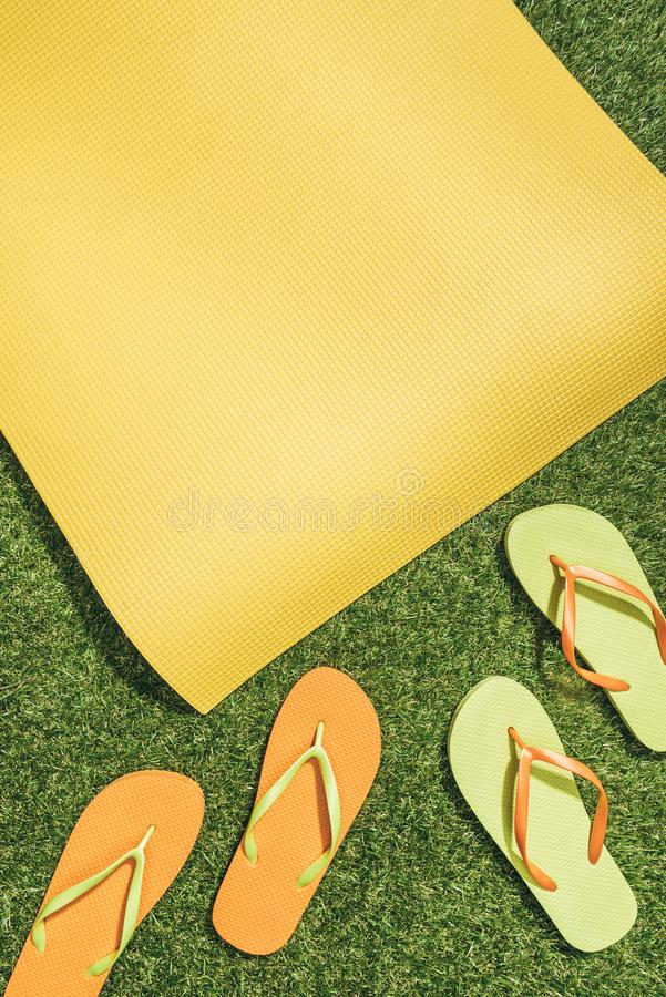 flat lay with yellow mat and flip flops stock images