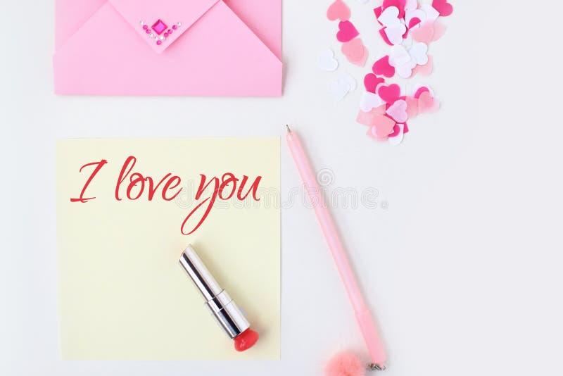 Flat lay: yellow paper, pink envelope, pen, pompom, perfume, lipstick, confetti hearts, lip print, i love you text. Making royalty free stock photo