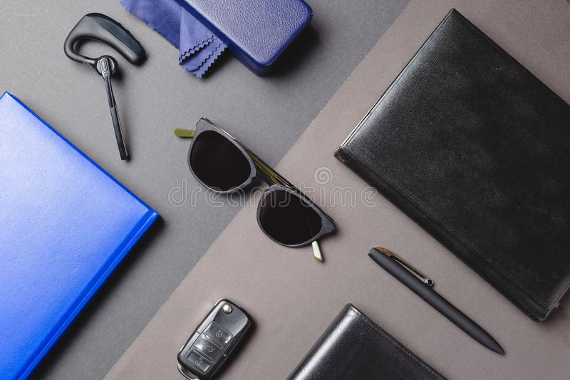 Flat layer of men accessories, sunglasses, agenda, car key, pen over creative background.  royalty free stock photography