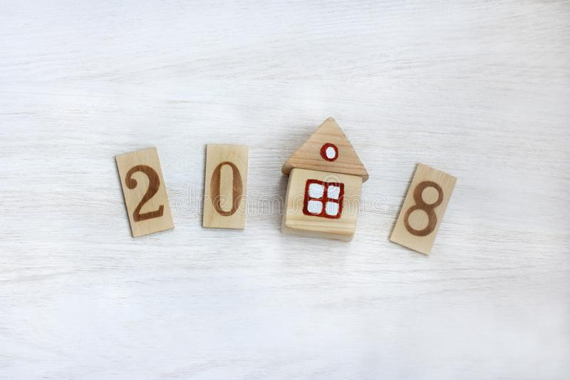 Personal property by 2018. Flat layout digits and house on a light wooden surface stock photos