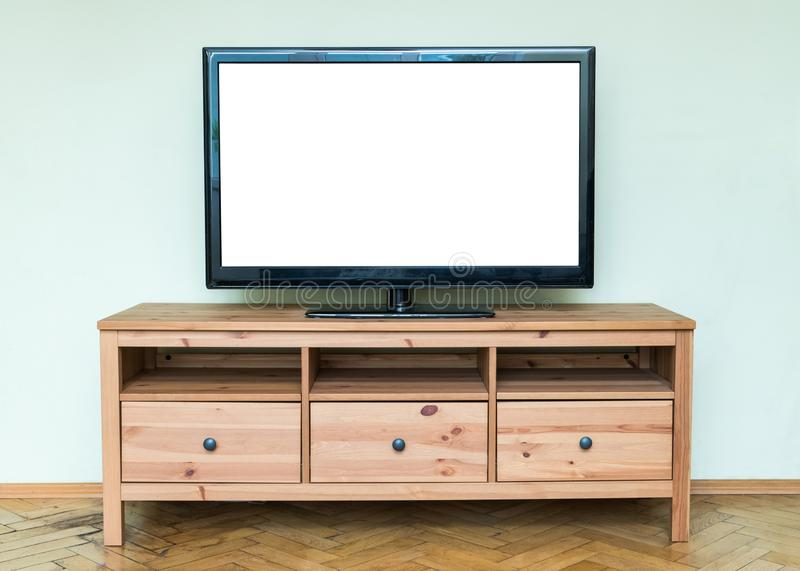 Flat LCD television on brown wooden cabinet in the living room w. Ith a white screen for copy text stock image