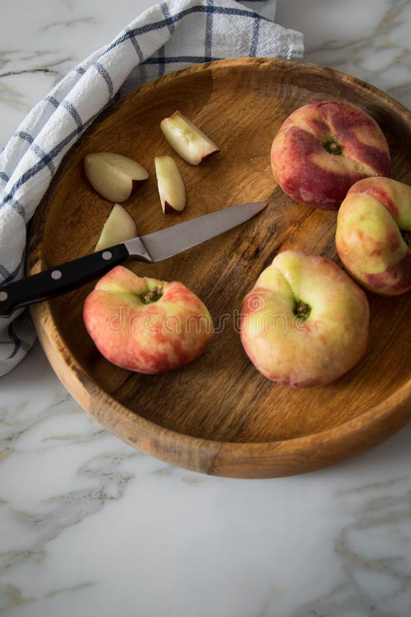 Flat peaches with knife and towel in wooden bowl on marble table stock image