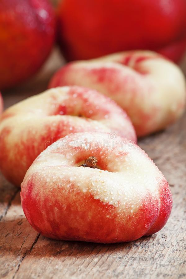 Flat pink nectarine on an old wooden background, selective focus. Food still life stock image