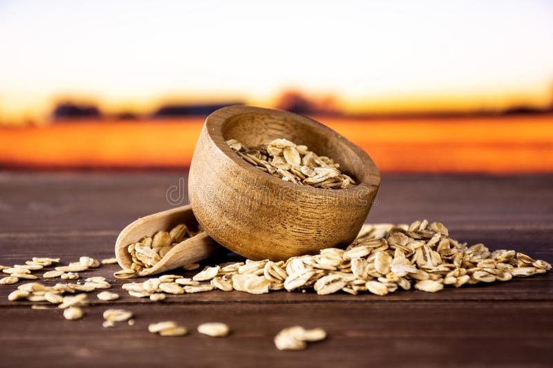 Flat raw rolled oats with autumn field behind stock image