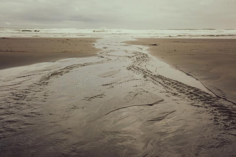 A Flat Meandering River leads down the Beach. A flat river winds its way across the sandy beach and makes its way out to the sea royalty free stock image