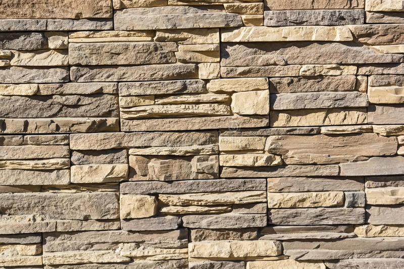 Flat rocks layered to form a solid wall. Close up beige stone wall formed from flat layered rocks royalty free stock image