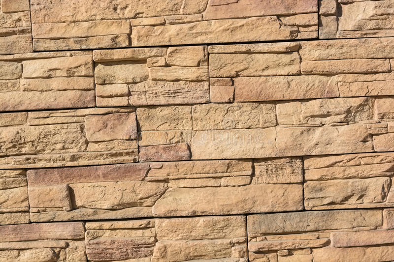 Flat rocks layered to form a solid wall. Close up beige stone wall formed from flat layered rocks royalty free stock photography