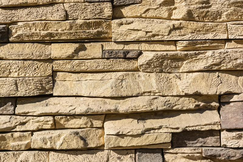 Flat rocks layered to form a solid wall. Close up beige stone wall formed from flat layered rocks stock images