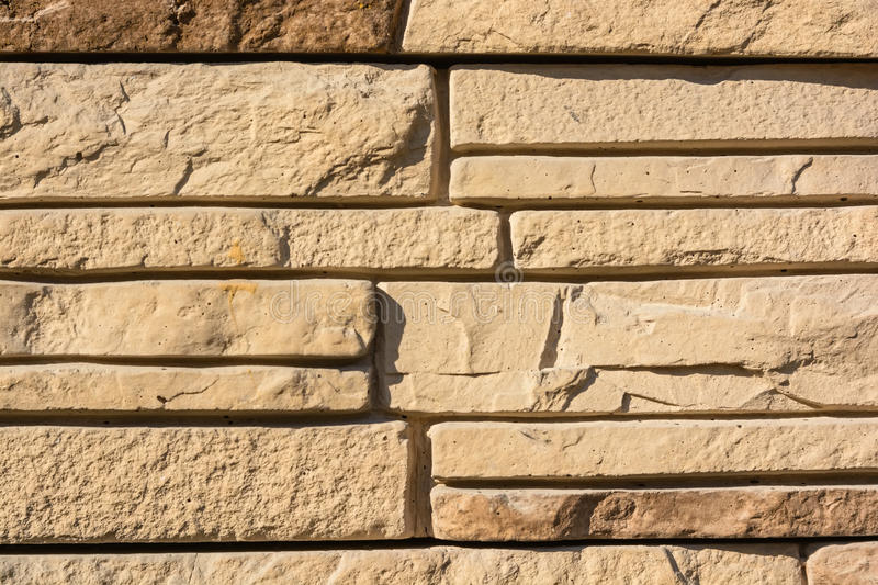 Flat rocks layered to form a solid wall. Close up beige stone wall formed from flat layered rocks stock image