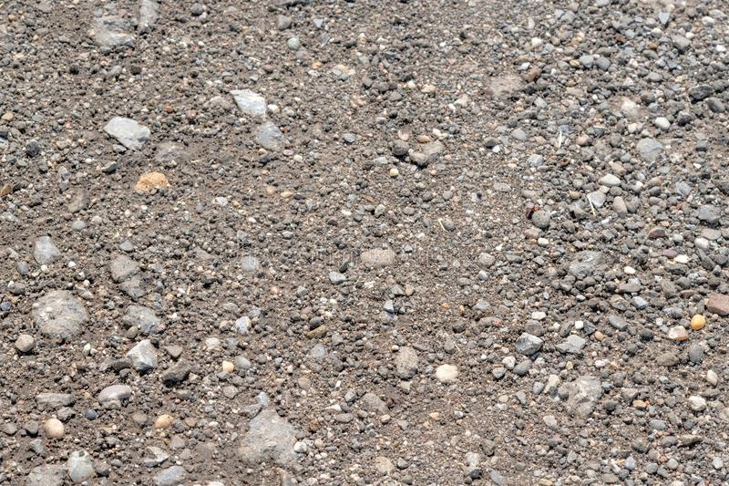 Flat rolled gray sandy soil with pebble stock image