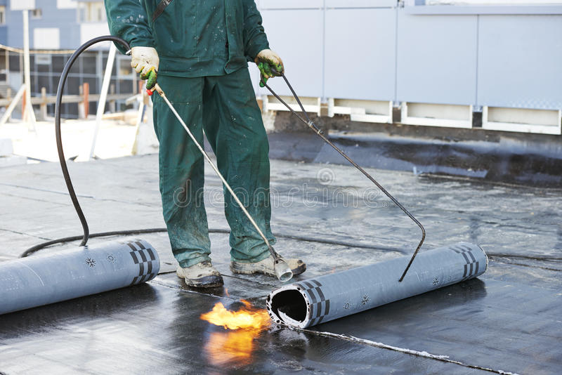 Flat roof covering repair works with roofing felt stock photo