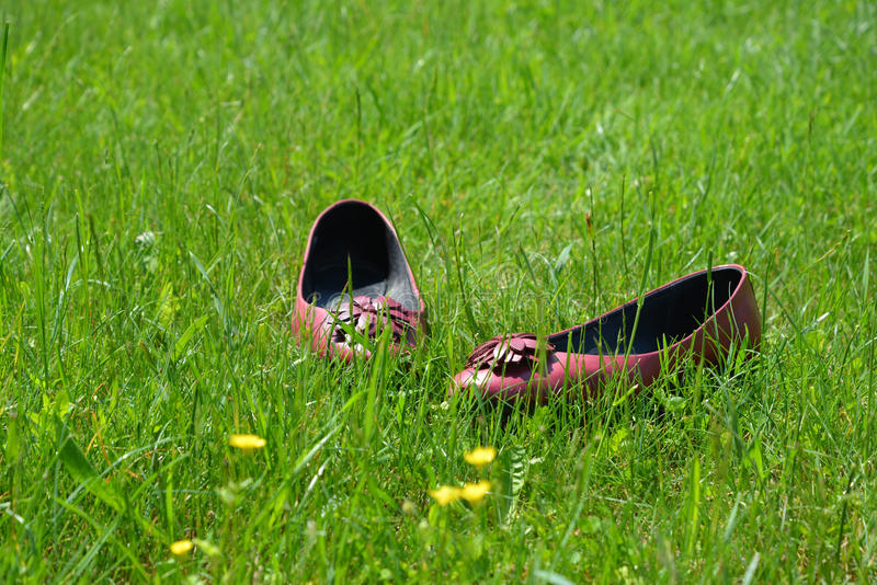 Flat shoes left in grass royalty free stock photography