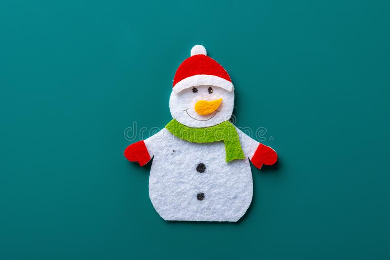 Flat smiling toy christmas snowman with green scarf on green stock images