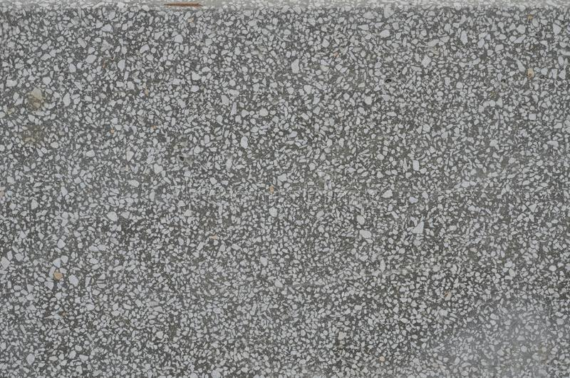 Flat textured gray surface of the artificial stone material. Flat surface of artificial stone made of mixture of mortar and small white marble pieces. Gray royalty free stock image