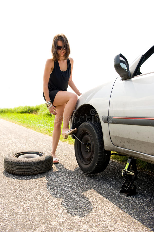 Flat tire. Brunette aggressively kicking the wrench to tighten the nuts of a flat tire she just replaced stock image