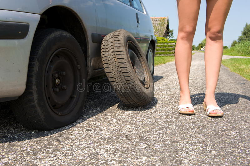 Flat tire. Long legged woman standing next to her car with a flat tire, the spare waiting to be put on royalty free stock image