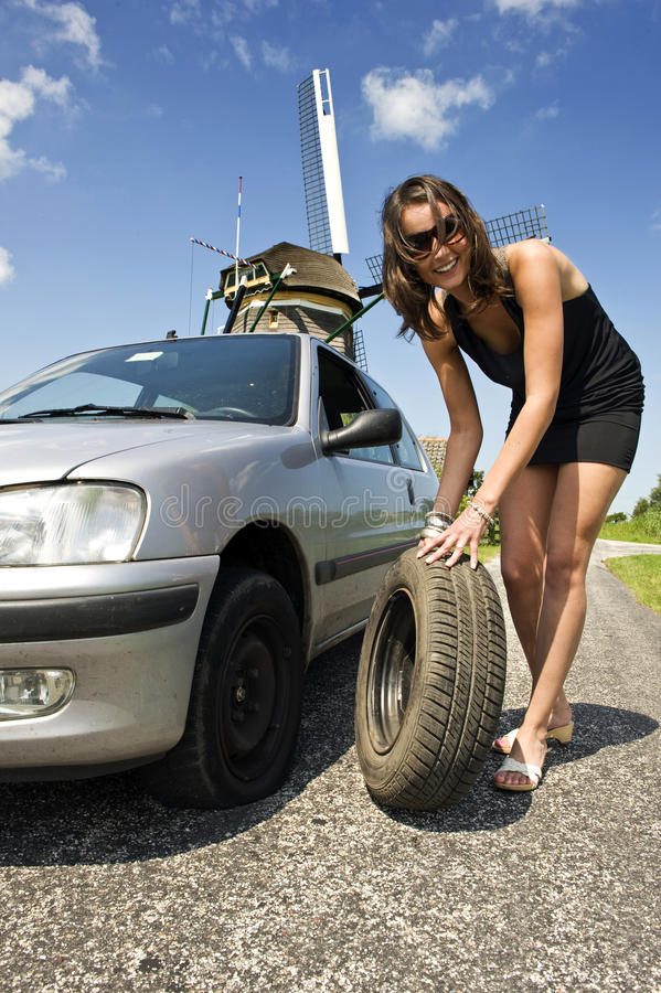 Flat tire. Young, confident woman, changing a flat tire on her car on a rural road with a wind mill in the backgrounc stock photo