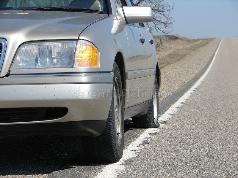 Flat Tire. A car on side of the road with a flat tire stock photo
