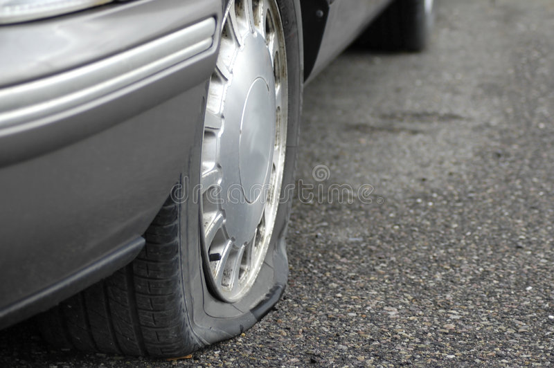 Flat Tire. Car on the road with a flat tire not moving stock image