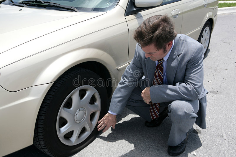 Flat Tire. A man dressed for a business meeting discovering a flat tire on his car stock image
