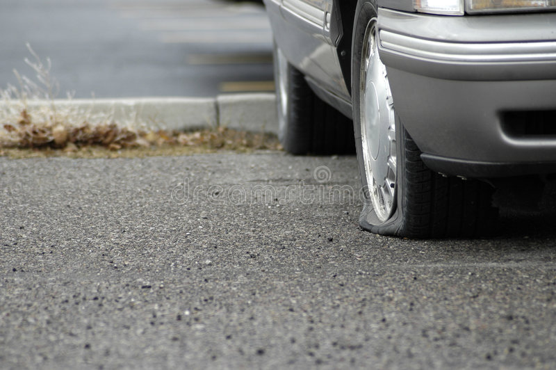 Flat Tire. Car parked on a roadway with a flat tire royalty free stock photo