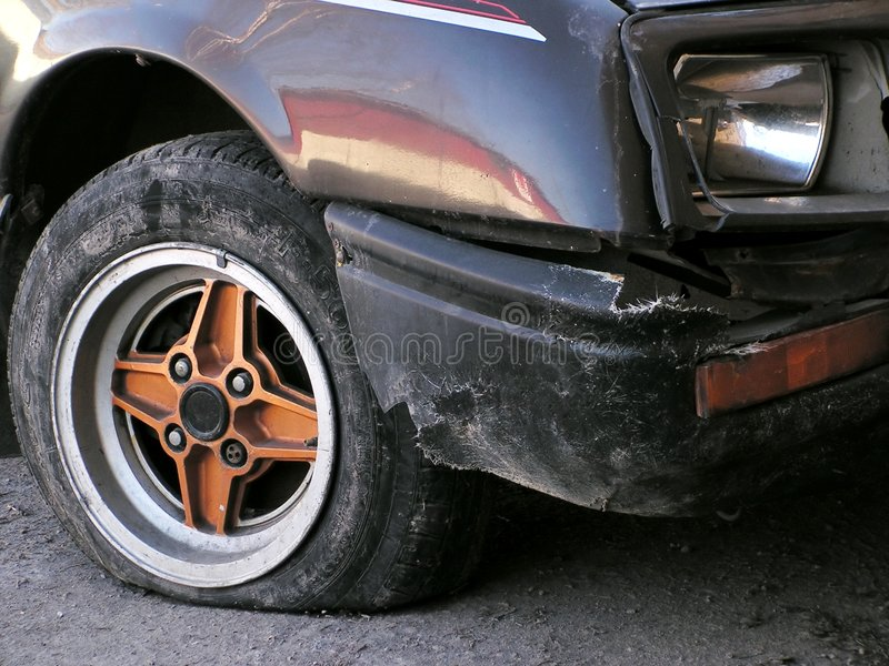 Flat tire. Broken car with flat tire, broken headlamp and ruined body stock image