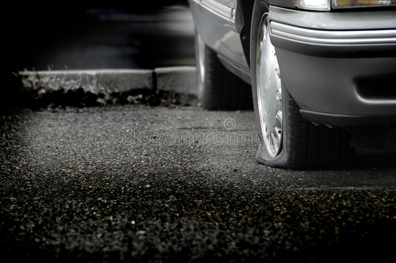 Flat Tire. Car parked on a roadway with a flat tire royalty free stock photography