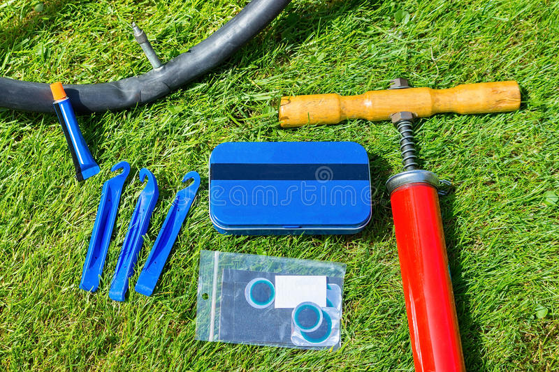 Flat tire of bicycle with repair material. Outdoors on grass royalty free stock images
